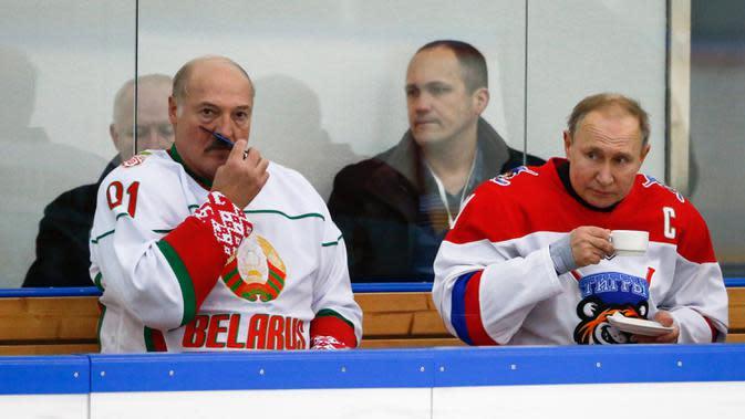 Presiden Rusia Vladimir Putin (kanan) dan Presiden Belarusia Alexander Lukashenko beristirahat saat mengikuti Night Hockey League di Sochi, Rusia, Jumat (7/2/2020). Putin dan Lukashenko bermain hoki bersama saat jeda pembicaraan ekonomi antara kedua negara. (AP Photo/Alexander Zemlianichenko, Pool)