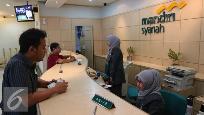 Petugas melayani nasabah di Bank Mandiri Syariah di Jakarta, Kamis (14/7). Sejumlah bank syariah mengaku siap menjadi bank persepsi, Jakarta, Kamis (14/7). (Liputan6.com/Angga Yuniar)