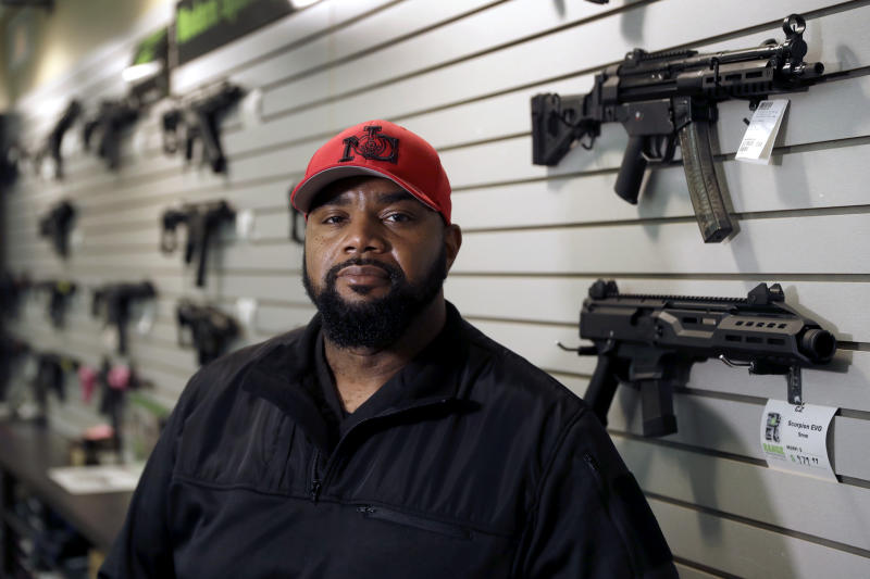 In this Sunday, Feb. 9, 2020 photo, Kevin Dixie poses for a portrait at The Range, a firearms retailer and gun range in Ballwin, Mo. Dixie considers himself agnostic when it comes to politics. But he's an ardent supporter of the Second Amendment who believes that gun rights are about empowering minority communities and ensuring freedom is available to every American, regardless of race, ethnicity or gender. (AP Photo/Jeff Roberson)