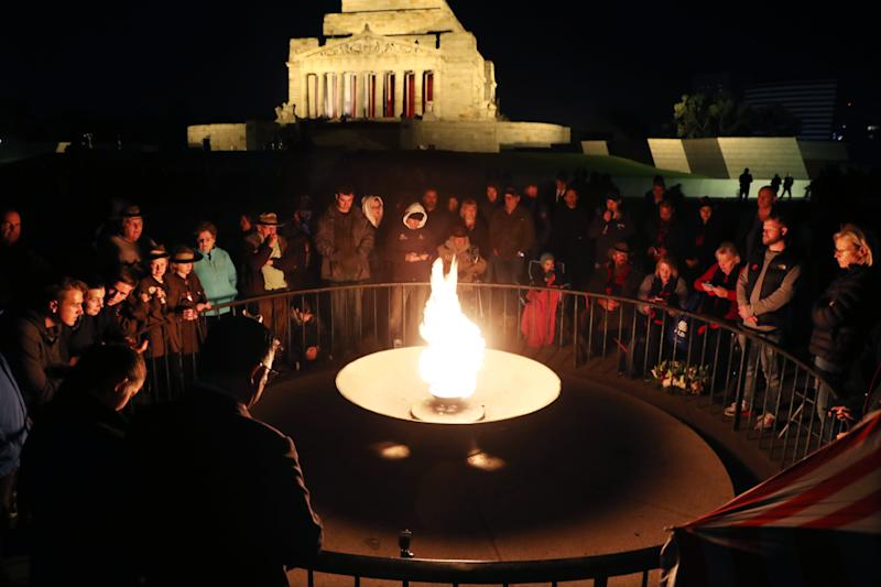 Crowds gather during the Anzac Day dawn service in front of the perpetual flame at the Shrine of Remembrance in Melbourne. Source: AAP