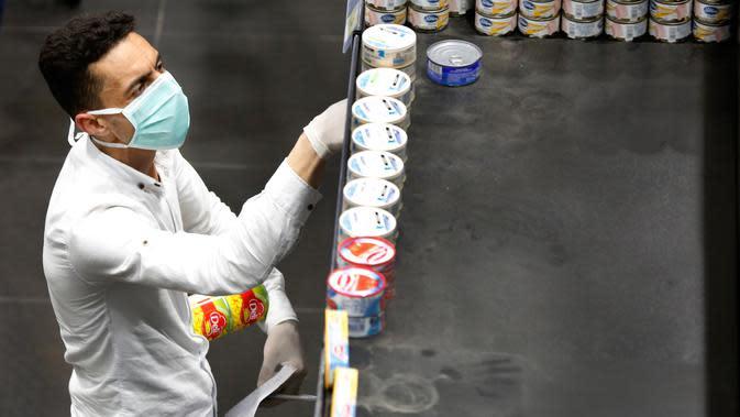 Seorang pria dengan masker dan sarung tangan berbelanja saat orang-orang mulai membeli persediaan di supermarket di Beirut, Rabu (11/3/2020). Dengan merebaknya virus Corona COVID-19 di Lebanon, warga mulai berbondong-bondong membeli makanan dan kebutuhan sehari-hari lainnya. (AP/Hussein Malla)