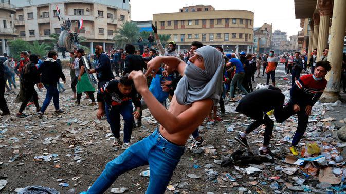 Demonstran antipemerintah melemparkan batu arah pasukan keamanan saat bentrok di Rasheed Street, Baghdad, Irak, Kamis (28/11/2019). Sebanyak 27 demonstran antipemerintah tewas ditembak mati oleh pasukan keamanan Irak dalam sehari. (AP Photo/Khalid Mohammed)