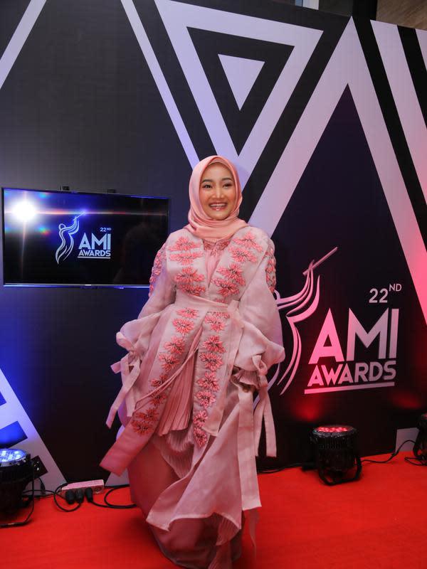 Selanjutnya ada Fathin Sidqia yang tampil cantik bernuansa pink. Mulai dari busana dan hijabnya berwarna senada. Senyuman bahagia terlihat di wajah Fathin malam tadi. (Adrian Putra/Fimela.com)