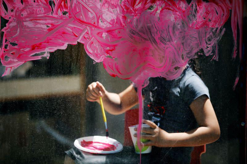 Girl paints on glass at her kindergarten in Jerusalem