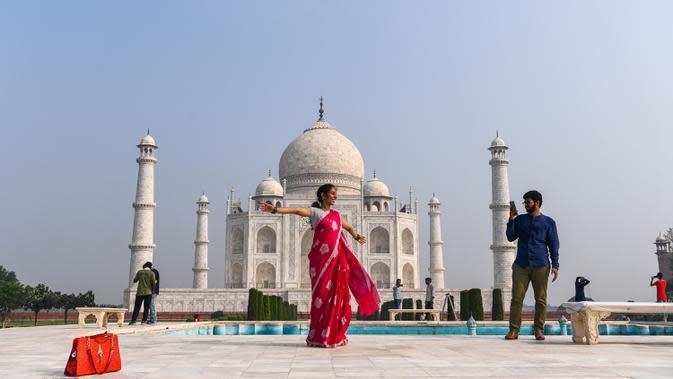 TAJ MAHAL KEMBALI DIBUKA: Turis mengunjungi Taj Mahal di Agra, India, Senin (21/9/2020). Taj Mahal kembali dibuka untuk umum pada Senin (21/9), dalam gerakan simbolis seperti biasa, bahkan ketika India tampaknya akan mengambil alih AS sebagai pemimpin global infeksi COVID-19. (Sajjad HUSSAIN/AFP)