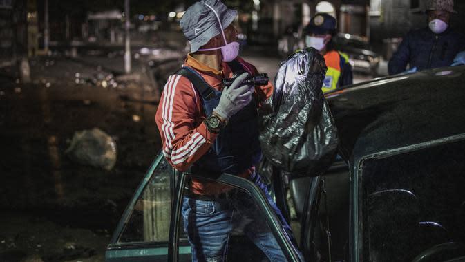 Petugas Departemen Kepolisian Metro Johannesburg (JMPD) memeriksa mobil warga. Afrika Selatan kini tengah dalam lockdown. (Marco Longari/AFP)
