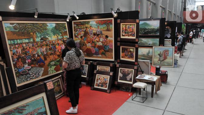Pengunjung mengamati karya lukis di salah satu stan yang dipamerkan dalam Indonesian Art Festival