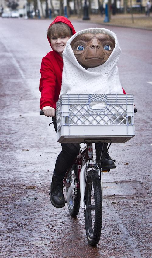 "This Oct. 19, 2012 photo made available on Oct. 22, shows a wax figure of ET from the 1982 Steven Spielberg film, ""E.T. the Extra-Terrestrial,"" being carried in the basket of a bmx bicycle by Madame Tussaud's employee Amy, in central London, marking the Blu-ray edition release of the film. Tussauds will launch an ET wax figure in London, Berlin, Amsterdam, Sydney and Hollywood on Oct. 22. (Photo by Joel Ryan/Invision/AP)"