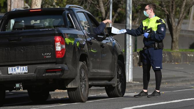 Petugas polisi menghentikan mobil untuk pemeriksaan izin selama tahap empat penguncian kota yang ketat karena wabah COVID-19 di Melbourne (11/8/2020). Negara bagian Victoria melaporkan 19 kematian akibat virus corona pada 11 Agustus. (AFP/William West)