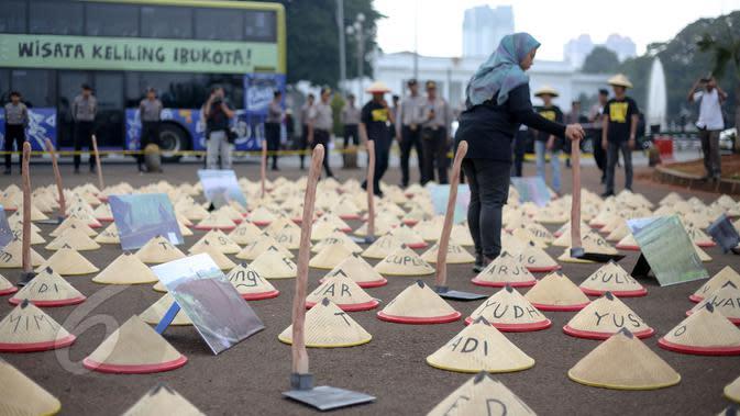 Warga Batang, Jawa Tengah membawa cangkul dan caping saat aksi di depan Istana Merdeka, Jakarta, Rabu (3/6/2015). Massa menuntut Presiden Jokowi menghentikan rencana pembangunan PLTU batubara di Batang. (Liputan6.com/Faizal Fanani)