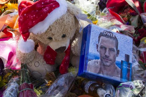 Flowers and messages are left at a memorial rally and car cruise in Valencia, Calif., Sunday, Dec. 8, 2013 to remember actor Paul Walker and his friend Roger Rodas, who died in a fiery car crash last Saturday. (AP Photo/Ringo H.W. Chiu)
