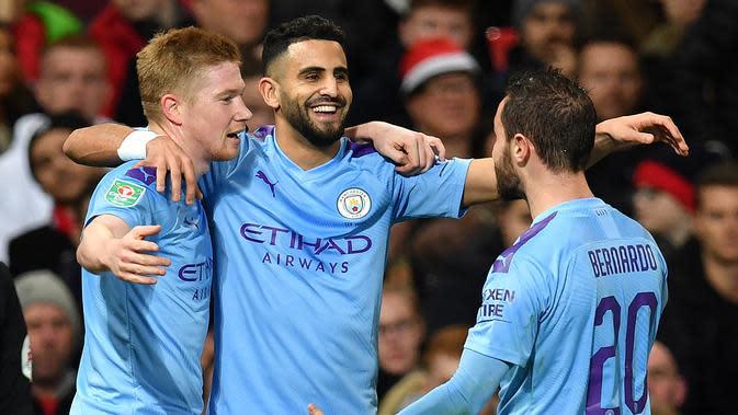 Gelandang Manchester City, Riyad Mahrez (tengah) berselebrasi dengan rekannya Kevin De Bruyne dan Bernardo Silva usai mencetak gol ke gawang Manchester United pada pertandingan leg pertama semifinal Piala Liga Inggris di Old Trafford, Rabu (8/1/2020). City menang 3-1 atas MU. (AFP/Paul Ellis)