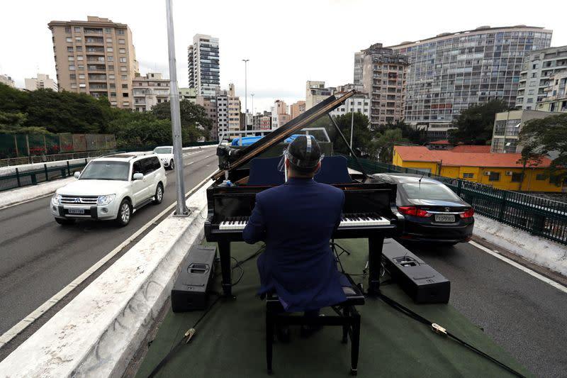 Pianist Rodrigo Cunha serenades from an open truck, in Sao Paulo