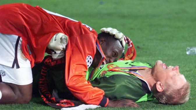 Pemain Manchester United, Peter Schmeichel dan Dwight Yorke melakukan selebrasi usai menjuarai Liga Champions di Stadion Camp Nou, Barcelona (26/5/1999). Manchester United menang 2-1 atas Bayern Munchen. (AFP/Eric Cabanis)
