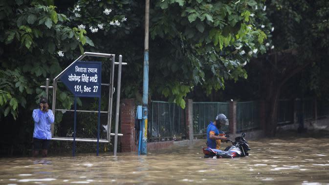Pengendara motor berdiri di jalan yang tergenang air setelah hujan monsun di Gurgaon di pinggiran New Delhi (19/8/2020). Jumlah korban dari banjir tahunan di seluruh Asia Selatan naik menjadi hampir 1.300. (AFP/Xavier Galiana)
