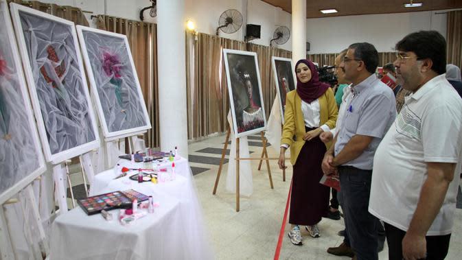 Orang-orang mengunjungi pameran seniman Palestina Kholoud al-Dasooqi di Gaza City, 11 Agustus 2020. Seniman Palestina asal Kota Khan Younis di Jalur Gaza itu menggelar pameran selama dua hari untuk mengungkap kekerasan terhadap perempuan melalui puluhan lukisan. (Xinhua/Rizek Abdeljawad)