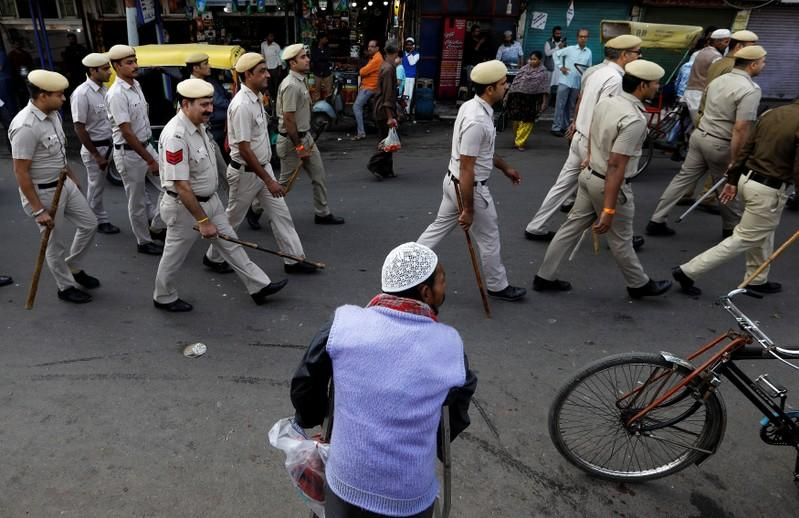 A Muslim man looks on as police officers conduct a flag march in a street outside Jama Masjid, before Supreme Court's verdict on a disputed religious site claimed by both majority Hindus and Muslim in Ayodhya, in the old quarters of Delhi
