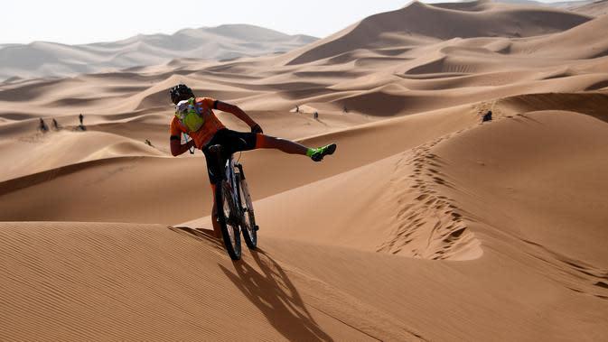 Pebalap mengendarai sepeda melintasi sepanjang bukit pasir pada etape 1 edisi ke 14 balap sepeda gunung Titan Gurun 2019 di sekitar Kota Merzouga, Maroko, Minggu (28/4/2019). Trek Titan Gurun 2019 sepanjang 640 km menghubungkan antara Merzouga dan Maadid. (Franck Fife / AFP)