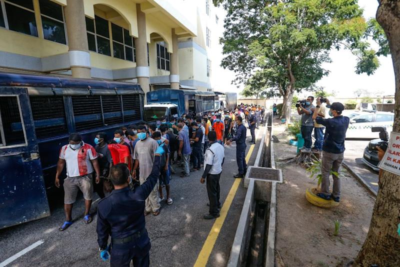 Police round up detainees who flouted the movement control order at the Butterworth Court Complex in Penang March 31, 2020. — Picture by Sayuti Zainudin