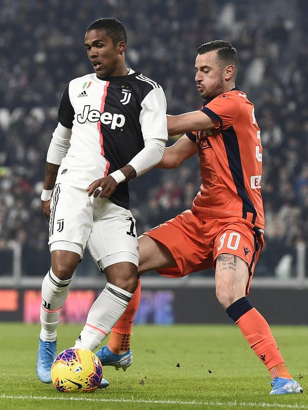 Pemain Juventus Douglas Costa (kiri) berebut bola dengan pemain Udinese Ilija Nestorovski pada pertandingan Coppa Italia 2019/2020 di Allianz Stadium, Turin, Italia, Rabu (15/1/2020).Juventus menang 4-0. (Fabio Ferrari/LaPress via AP)