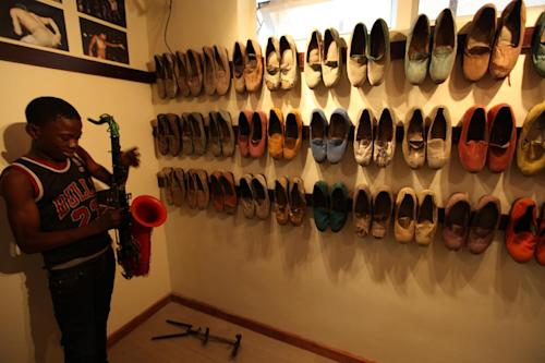 A young man picks up a saxophone once owned by singer Fela Anikulapo-Kuti as the musician's shoes hang in the background in Lagos, Nigeria, on Monday, Oct. 15, 2012. The family of late Afrobeat singer Fela Anikulapo-Kuti celebrated the opening of the Kalakuta Museum on Monday in Lagos in the home the musician once lived in. The opening of the museum comes during Felabration, an annual music festival honoring the singer. (AP Photo/Jon Gambrell)