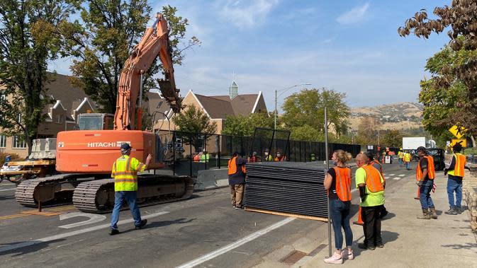 Pekerja mendirikan barikade beton dan pagar sementara di luar kompleks Universitas Utah di Salt Lake City, Senin (5/10/2020). Universitas Utah akan menjadi tuan rumah debat calon wakil presiden petahana Mike Pence dan Senator California Kamala Harris akan digelar pada Rabu 7 Oktober. (Daniel SLIM /