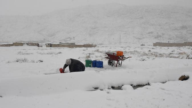 Seorang pria mengambil air minum saat hujan salju di Quetta, Pakistan, Minggu (12/1/2020). Sebanyak 30 orang dilaporkan tewas akibat cuaca buruk yang melanda Pakistan. (Banaras KHAN/AFP)