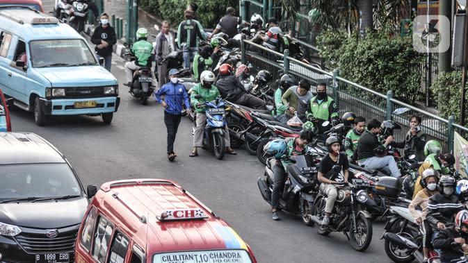 Pengemudi ojek online (ojol) memenuhi bahu jalan saat menunggu penumpang di kawasan Cililitan, Jakarta, Rabu (16/9/2020). Minimnya pengawasan membuat masih banyak pengemudi ojol yang berkerumun saat menunggu penumpang meski Pemprov DKI Jakarta telah melarangnya. (merdeka.com/Iqbal S. Nugroho)