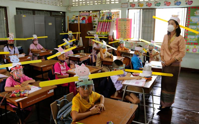 A teacher and students wearing hats designed for space keeper, practice social distancing to help curb the spread of the coronavirus at Ban Pa Muad School in Chiang Mai, north of Thailand - Wichai Taprieu/AP