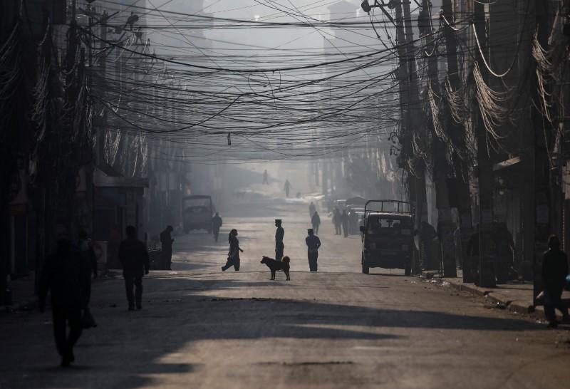 People walk on a deserted road on the fourth day of the lockdown imposed by Nepal's government amid concerns on the spread of the coronavirus disease (COVID-19), in Kathmandu