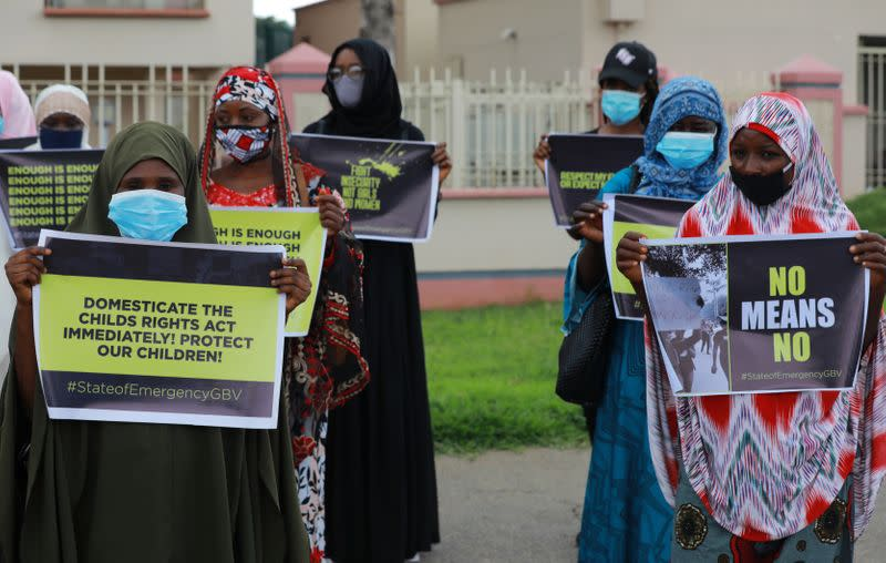Protesters  carry banners as they stage a demonstration to raise awareness about sexual violence in Abuja