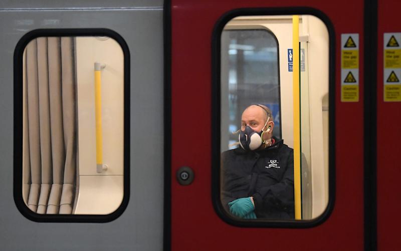 A member of the public wears a a protective mask on the Tube in London - Getty