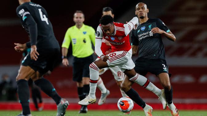 Gelandang Arsenal, Joe Willock mengggiring bola saat bertanding melawan Liverpool pada pertandingan lanjutan Liga Inggris di Stadion Emirates di London (15/7/2020). Arsenal menang tipis 2-1 atas Liverpool. (Paul Childs/Pool via AP)