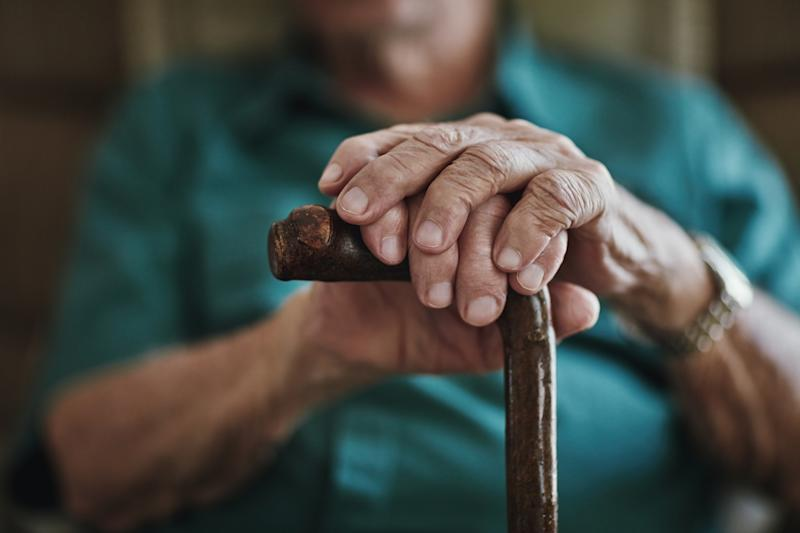 Photos shows an elderly man leaning on a walking stick with both hands.