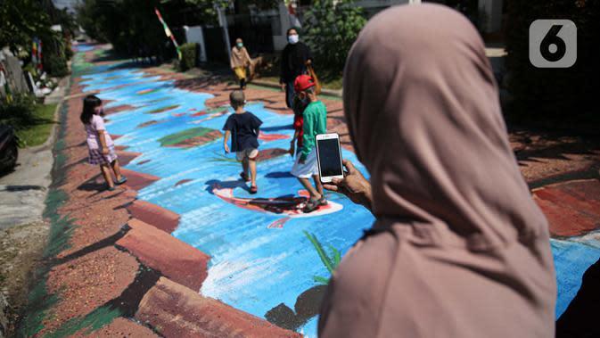Warga berfoto di atas jalan yang telah dilukis mural di Jalan Keuangan, Cilandak, Jakarta, Rabu (26/8/2020). Museum Basoeki Abdullah bekerjasama dengan Perupa Jakarta Raya membuat mural dengan memanfaatkan ruang publik di sepanjang jalan menuju museum Basoeki Abdullah. (Liputan6.com/Faizal Fanani)