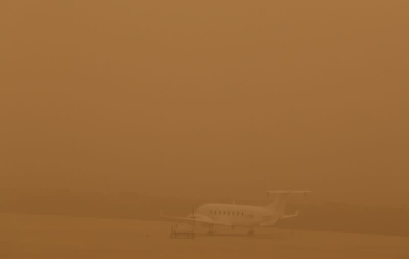 "A plane is seen parked on a tarmac during a sandstorm blown over from North Africa known as ""calima"" at Las Palmas Airport"