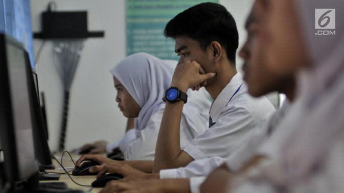 Sejumlah siswa kelas XII mengerjakan soal Bahasa Indonesia saat mengikuti Ujian Nasional Berbasis Komputer (UNBK) di SMKN 50 Jakarta, Senin (25/3). Kemendikbud mengatur UNBK tingkat SMK dilaksanakan serentak dalam empat hari mulai 25 sampai 28 Maret 2019. (merdeka.com/Iqbal S. Nugroho)
