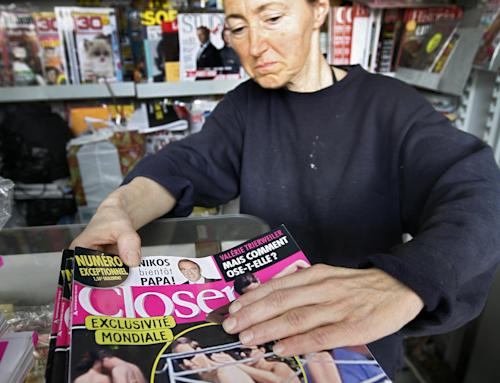 "FILE - In this Sept. 18, 2012 file photo, a news stand worker checks copies of Closer magazine which published 14 photos of a partially clad Kate Duchess of Cambridge in its pages, in Nice, southern France. A prosecutor's office says Thursday, April 26, 2013 a French judge has placed under investigation the photographer and publishing company behind unauthorized topless photos of Prince William's wife, Kate, that appeared in ""Closer"" magazine in France last September. (AP Photo/Lionel Cironneau, File)"