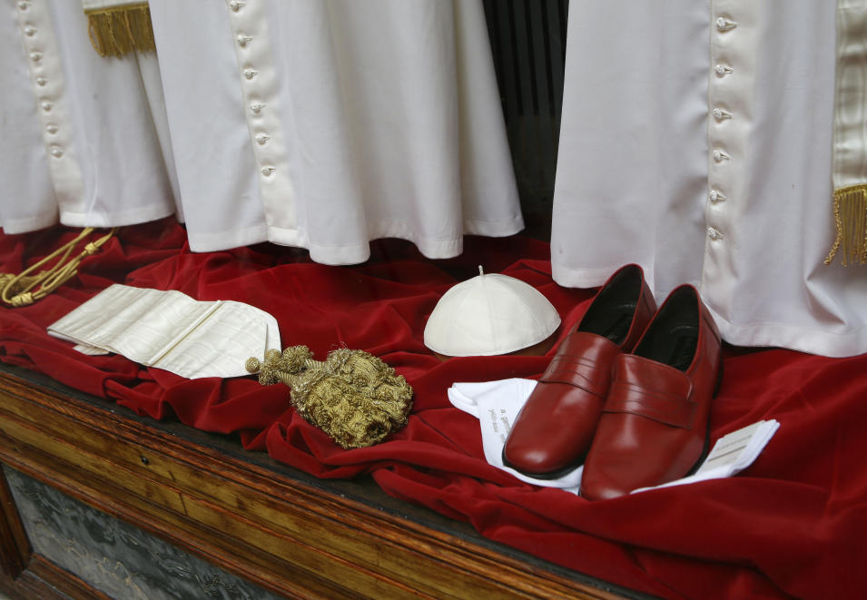 Papal shoes and a white skull cap are seen beneath three sets of papal outfits - small, medium and large sizes - which will be sent to the Vatican for the new pope, are displayed in the Gammarelli tailor shop window, in Rome, Monday, March 4, 2013. For over a half century the Gammarelli family has produced the pope robes in three different sizes that are delivered before the conclave meets, in order to fit the newly elected popes. (AP Photo/Andrew Medichini)