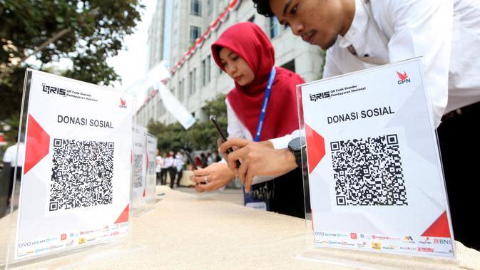 Karyawan BI melakukan transaksi menggunakan QR Code Indonesian Standard (QRIS) di kantor BI, Jakarta, Sabtu (17/8/2019). QRIS merupakan transformasi digital pada Sistem Pembayaran Indonesia sangat membantu percepatan pengembangan ekonomi dan keuangan digital di Indonesia. (Liputan6.com/HO/Rizal)
