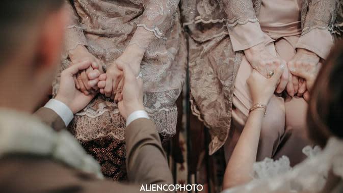 Suasana akad nikah pun Nampak begitu khidmat. Pasangan pengantin baru ini juga tampak melakukan sesi sungkeman kepada orangtua. Seperti di foto ini, Marcell dan Nabila terlihat sedang menggenggam tangan ibunda mereka. (Instagram/aliencophoto)