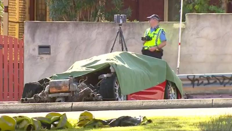 A police officer with a camera stands next to the remains of a red Ferrari after a fatal car crash in Perth.
