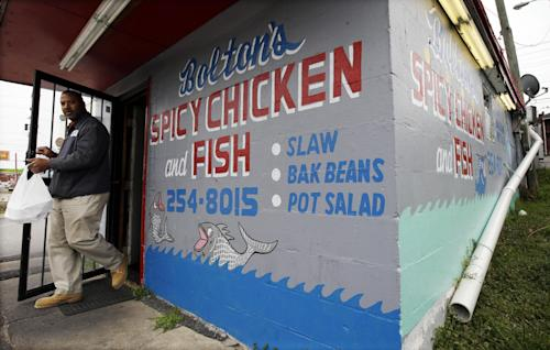 In this Friday, March 22, 2013, photo, a customer carries out an order from Bolton's Spicy Chicken and Fish restaurant in Nashville, Tenn. Hot chicken -- fried chicken with varied amounts of seasoning that make the heat level run from mild to extra hot -- is a signature dish of Nashville. (AP Photo/Mark Humphrey)