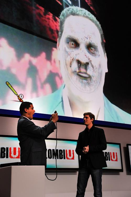 "FILE - In this June 5, 2012 publicity file photo provided by Nintendo of America, Reggie Fils-Aime, Nintendo of America's President and Chief Operating Officer, left, tests out an interactive feature of ""ZombiU,"" an upcoming Ubisoft game for the Wii U console, during the Nintendo All-Access Presentation at E3 2012 in Los Angeles. Using facial recognition, the feature transforms the player into a gruesome zombie. (AP Photo/Nintendo of America, Vince Bucci, File)"