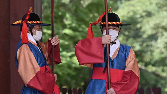 KASUS COVID-19 DI KOREA SELATAN: Anggota 'penjaga istana' yang mengenakan masker berdiri untuk turis di gerbang utama Istana Deoksugung di Seoul (4/9/2020). Korea Selatan melaporkan 198 kasus Covid-19 baru pada 4 September, hari ke-22 berturut-turut meningkat tiga digit. (AFP/Jung Yeon-je)