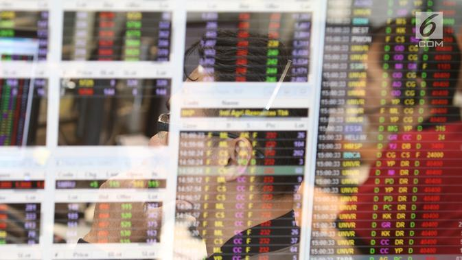 Pekerja mengamati pergerakan Indeks Harga Saham Gabungan (IHSG) di salah satu perusahaan Sekuritas, Jakarta, Rabu (14/11). Indeks Harga Saham Gabungan (IHSG) berhasil bertahan di zona hijau pada penutupan perdagangan hari ini. (Liputan6.com/Angga Yuniar)