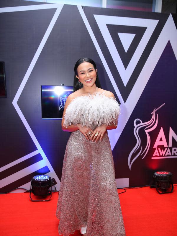 Yura Yunita terlihat glamor hadir di red carpet AMI Awards 2019, gaun panjang yang dikenakan manis dengan aksen bulu-bulu pada bagian dadanya. Rambut panjangnya pun dibiarkan terurai lurus. (Adrian Putra/Fimela.com)
