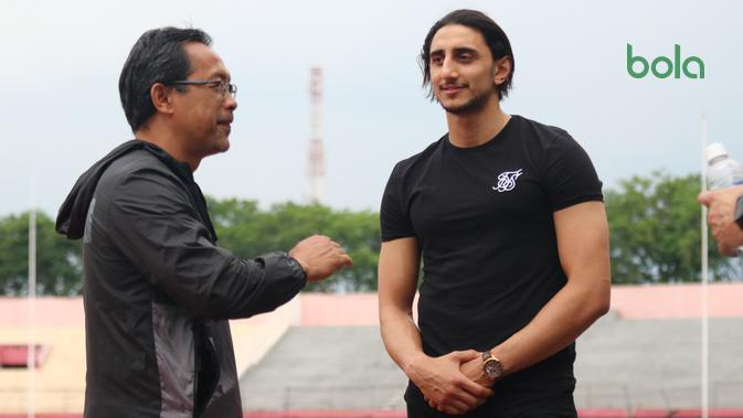 Pelatih Persebaya Surabaya, Aji Santoso, tengah berbincang dengan pemain asing anyar, Mahmoud Eid, saat sesi latihan, Senin (6/1/2020). (Bola.com/Aditya Wany)