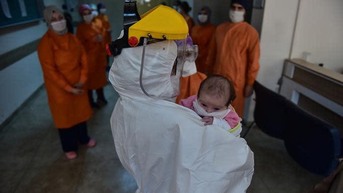 Petugas medis menggendong bayi berusia 45 hari di Rumah Sakit Prof. Cemil Tascioglu Okmeydani di Istanbul, Turki, Selasa (12/5/2020). Bayi itu keluar dari unit perawatan intensif (ICU) rumah sakit tersebut pada Selasa (12/5) setelah menjalani perawatan infeksi COVID-19 selama sembilan hari. (Xinhua)