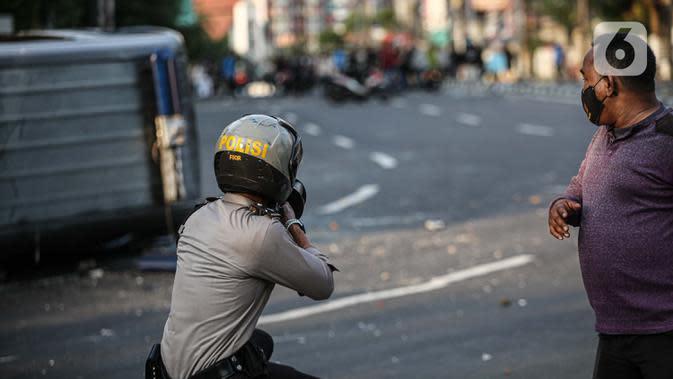 Polisi menembak ke arah massa saat bentrok di kawasan Pejompongan, Jakarta, Rabu (7/10/2020). Belum bisa dipastikan apakah aksi tersebut berkaitan dengan isu aksi penolakan pengesahan UU Omnibus Law Cipta Kerja. (Liputan6.com/Faizal Fanani)